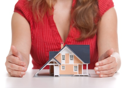 realty residence: Woman protecting model of house. Realty investment protection concept. Selective focus on house. Stock Photo