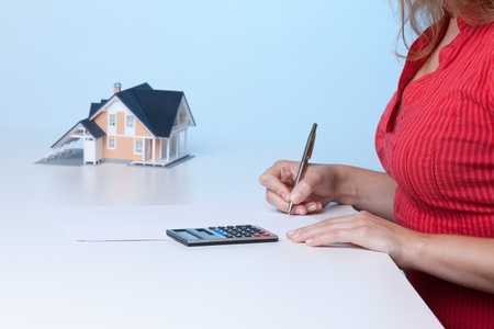 Real estate broker calculating amount of payments family house mortgage. Focused on calculator. photo