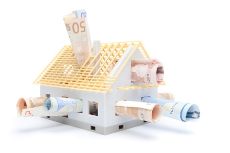 Housing finance, building savings and realty financing (investments) concept. Money and model of the family house. photo