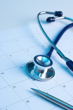 checkup: Routine medical exam represented by part of stethoscope, calendar and pen. Family doctor workplace.  Stock Photo