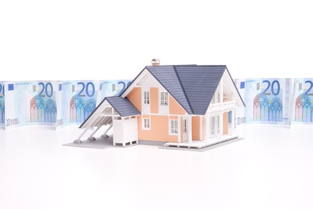 household insurance: Housing finance, building savings and realty financing (investments) concept. Money wall and model of the family house.