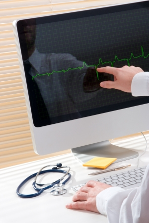 Doctor working with computer and electrocardiogram photo