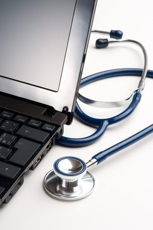 general practitioner: Part of stethoscope and laptop on white desk - general practitioner doctor workplace