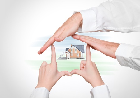 realty residence: Couple protect home - male and female hands creating house, model of family house in center