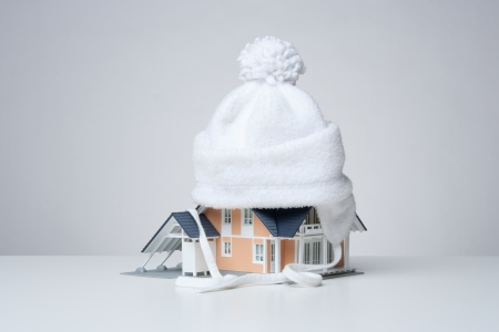 economize: Baby cap isolate model of the house against heat leak - house insulation concept. Gray background.