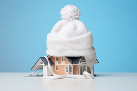 insulation: Baby cap isolate model of the house against heat leak - house insulation concept. Blue background. Stock Photo
