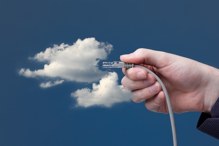 Cloud computing concept. Hand with ethernet cable connecting into cloud. photo