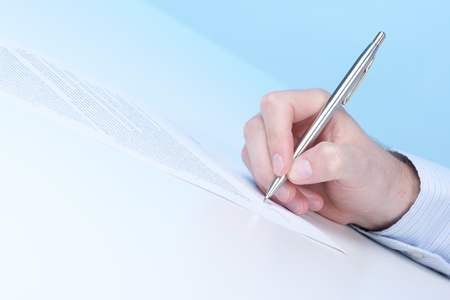 underwrite: Signing a contract - hand with pen Stock Photo