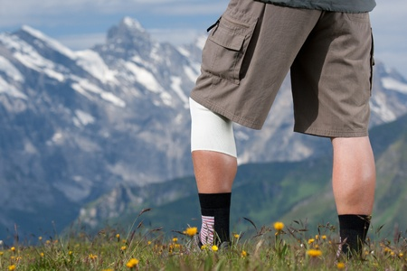 swiss alps: Elderly hiker with bandage on knee in Swiss Alps Stock Photo