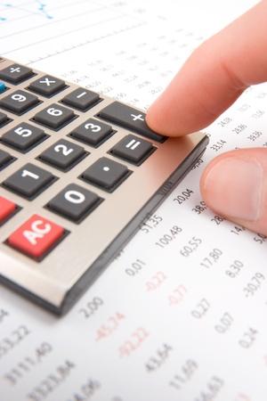 Business analyst calculate revenue - finger push button plus on calculator photo