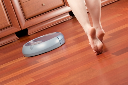 go inside: Woman go round home washing robot in cleaning action, saving her time. Genuine living room wooden floor (jatoba). Selective focus on robot. Stock Photo