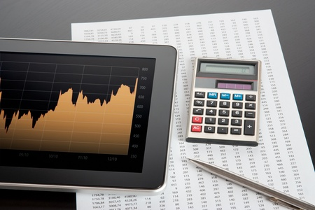 Modern stock market analyze with digital tablet, calculator, pen and printed data sheet photo