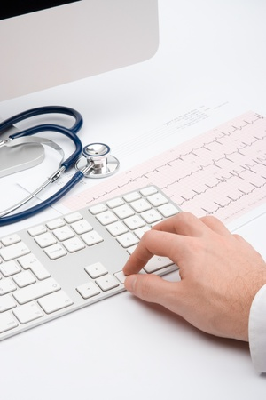 work checkup: Doctor working with computer and electrocardiogram