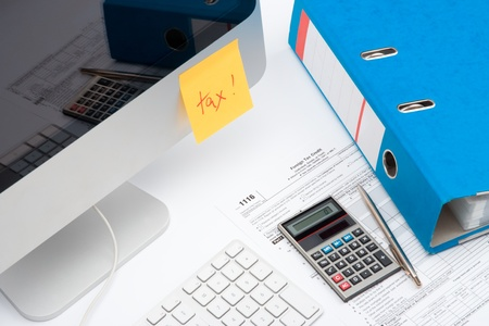 mention: Tax concept - sticky notes with word tax, tax form, part of computer, keyboard, calculator, office folder and pen