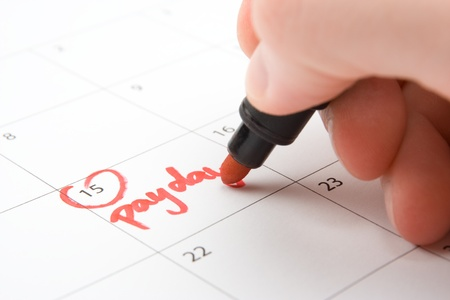 existence: Hand write payday in to calendar (lead a hand-to-mouth existence) Stock Photo