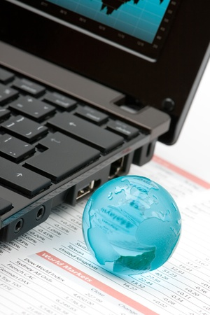 World markets analyze concept - laptop, glass globe and printed data sheet photo