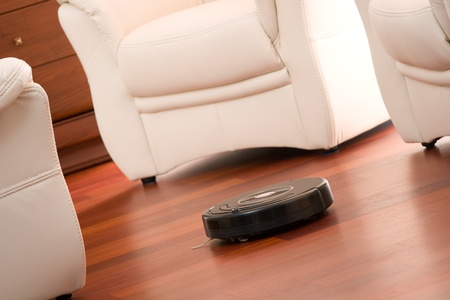 Home vacuum cleaning robot in action on genuine living room wooden floor. Selective focus on robot. photo