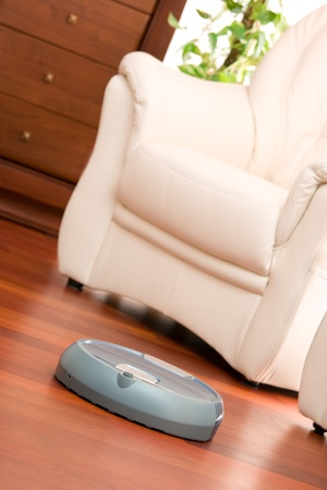 Home washing robot in cleaning action on genuine living room wooden floor. Selective focus on robot. photo