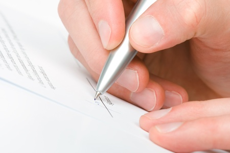 Signing a contract - hand with pen closeup photo