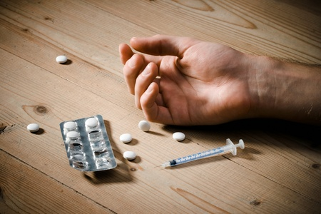 substance: Drug abuse concept - passive hand on floor, pills and injection