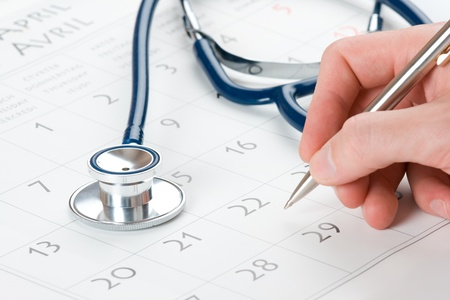 doctors tool: Doctor write medical exam results in calendar Stock Photo