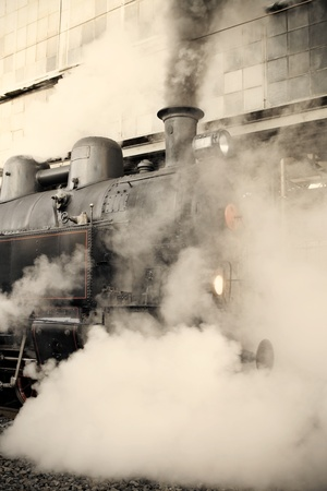 railway engine: Steam locomotive at the railway station wrapped up in cloud - vintage retro tinting Stock Photo