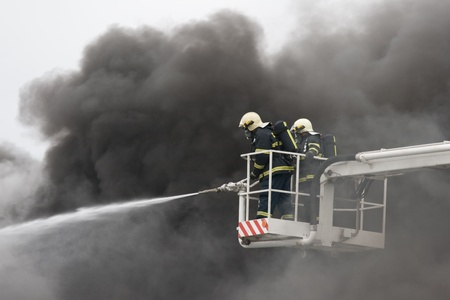 Two firefighters on ramp and smoke in background Stock Photo