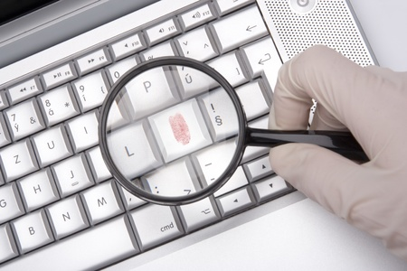 Laptop keyboard with fingerprint enlarged by magnifying glass - computer criminality concept Stock Photo - 11850297