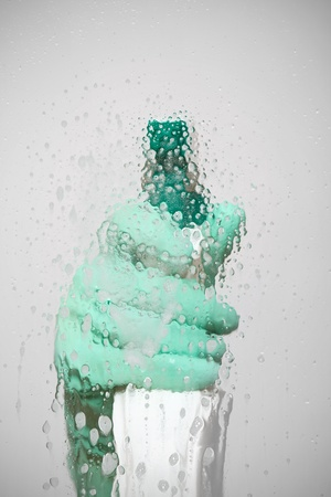 cleaning products: Sanitation worker spray cleaning agent on glass surface