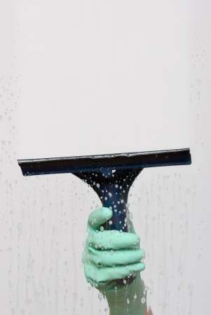 window cleaning: Window washer hand with squeegee clean window Stock Photo