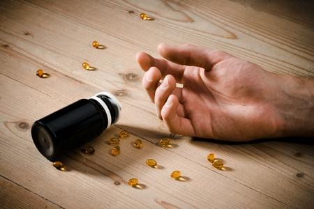 overdosering: Vitaminen overdosis concept - passieve hand op vloer en morsen pillen Stockfoto