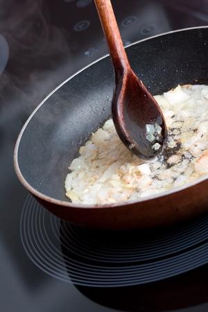 fryingpan: Fried onion in frying-pan and spoon Stock Photo