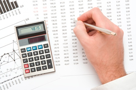 spreadsheets: Concept of business analyst - hand with pen; calculator, sheet and graph from top view Stock Photo