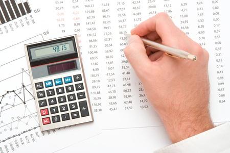 hoja de calculo: Concepto de analista de negocios - la mano con la pluma, calculadora, hoja y el gr�fico de vista superior Foto de archivo