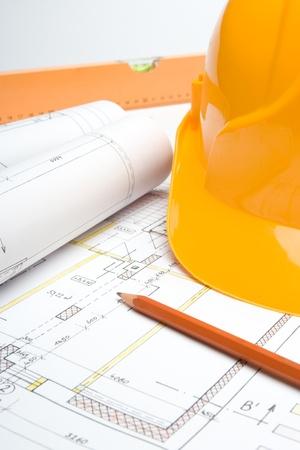 superintendent: Blueprints of architecture interior, pencil, protective helmet and bubble level