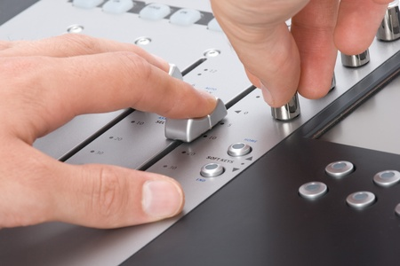 Sound engineer with hands on fader and knob photo