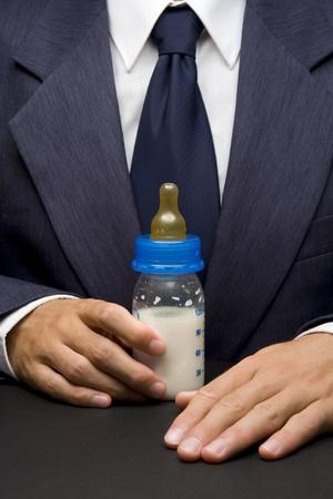 nursing bottle: Junior manager concept - businessman holding nursing bottle with milk