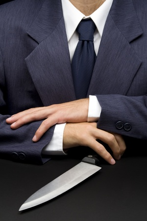 transact: Unfair manager do business with knife on table, concept Stock Photo