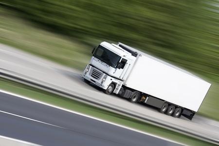 camión: Blanco cami�n en la carretera (fondo desenfocado) - Transporte Foto de archivo