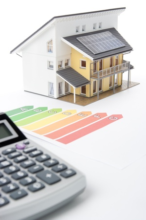 Calculator, energy efficiency rating graph and model of the active house.  Focused oh graph and part of the house. photo