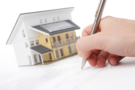 agency agreement: Man confirm mortgage contract (estate agency client sign contract). Model of the active (energy positive) house in background out of focus. Stock Photo
