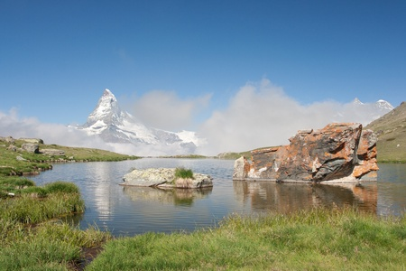 Matterhorn mountain with morning clouds reflecting in Stellisee, Alps, Switzerland photo