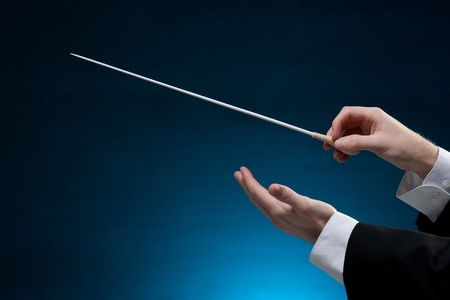 composer: Male orchestra conductor hands, one with baton. Blue background.
