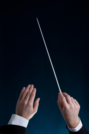 nonverbal communication: Male orchestra conductor hands, one with baton. Blue background.  Stock Photo