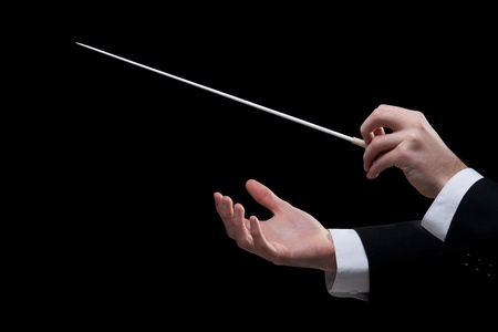 Male orchestra conductor hands, one with baton. Black background.
