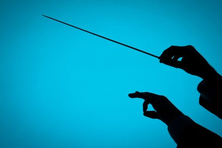 conductor: Male orchestra conductor hands, one with baton. Silhouette against blue background. Stock Photo