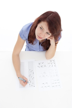 iq: Young woman (student) filling IQ test - intelligence measuring concept. Focused on woman face, top view, white background.  Stock Photo
