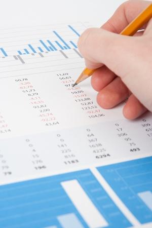 Concept d'analyste d'affaires - la main avec un crayon, tableau et des graphiques.