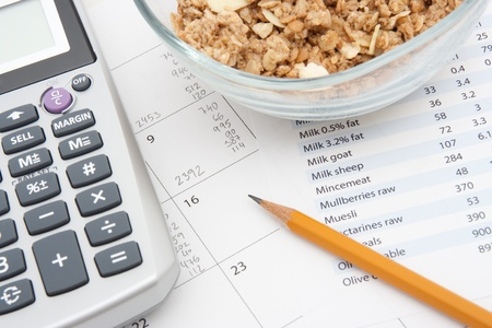 supervise: Healthy eating concept - calendar with daily nutrition intake, nutrition chart, muesli in glass bowl and calculator  Stock Photo