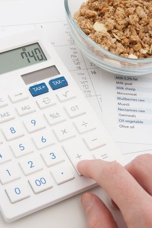 supervise: Healthy eating concept - man calculate his daily nutrition intake  Muesli in glass bowl, calculator, calendar and nutrition chart